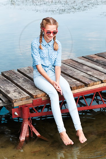 Young smiling girl sitting on jetty over the lake and dipping feet in water on sunny day in the summertime photo