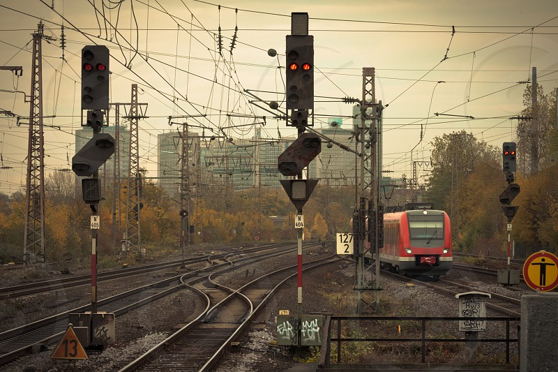 Mobile photography lo-fi styled image of a red commuter train on an urban railway track with confusing lines and overhead cables and a red signal light photo
