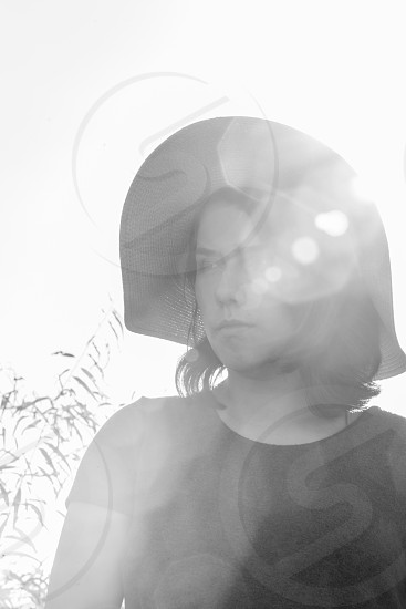 Girl in sun hat in a sea of sunflowers black and white with sunflare. photo
