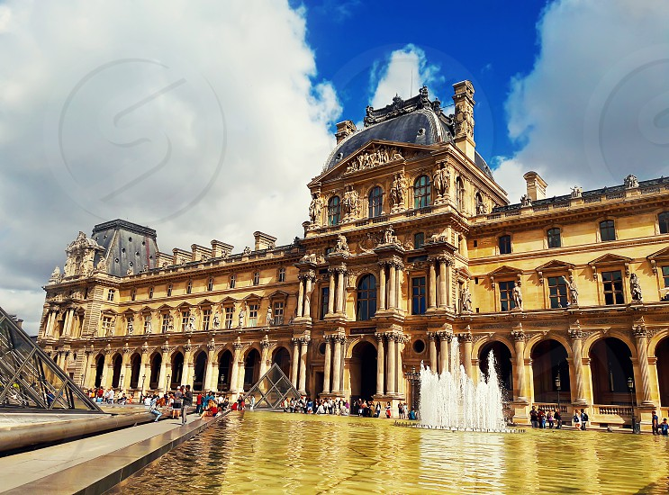 Richelieu wing of the Louvre building with fountain tourists and the glass Pyramid in Paris France. photo