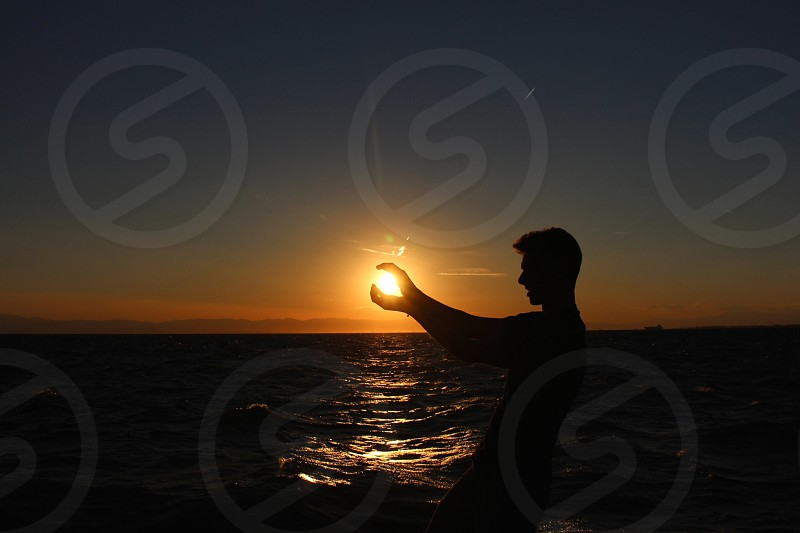 silhouette of man trying to hold sun photo