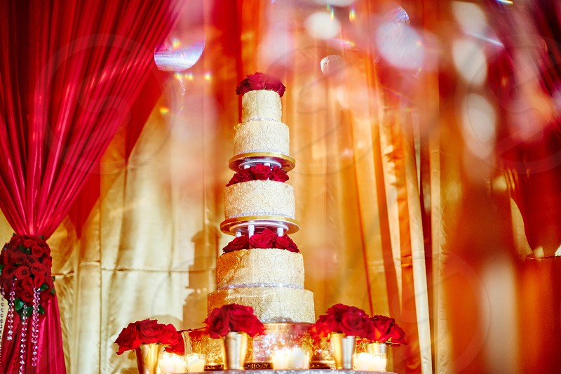 Luxury wedding cake with red roses and candle light decoration The red gold curtain in background with some bokeh in foreground photo