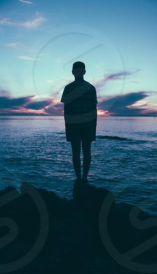 man's silhouette standing beside blue sea photo