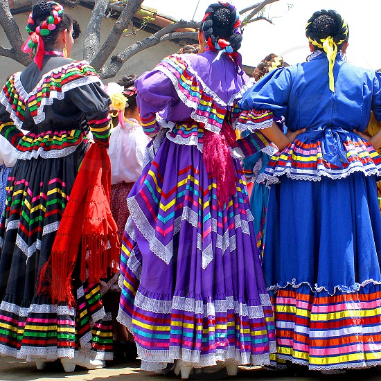Three women dressed in colorful folkloric dresses for a fiesta are seen from behind. photo