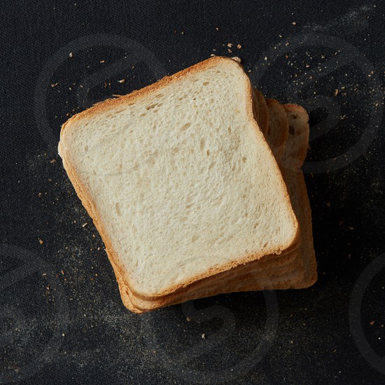Top view of many slices of white bread isolated on black background. Loaf of sliced bread for making sandwiches for breakfast lunch dinner etc. photo