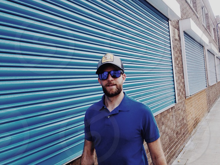 Guy in front of blue shutters wearing shades and cap photo