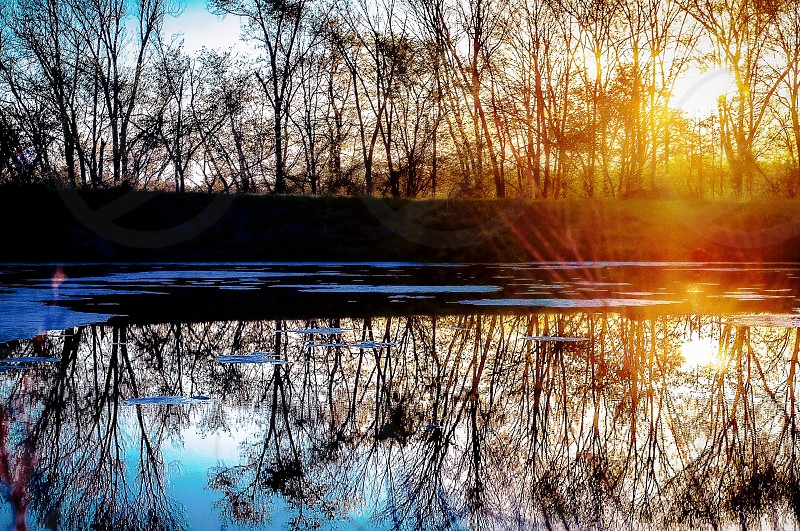 ARTISTIC SKIES | I love this image for it's cool and warm tones all in one and the reflection in the water adds even more color and sun flare. photo