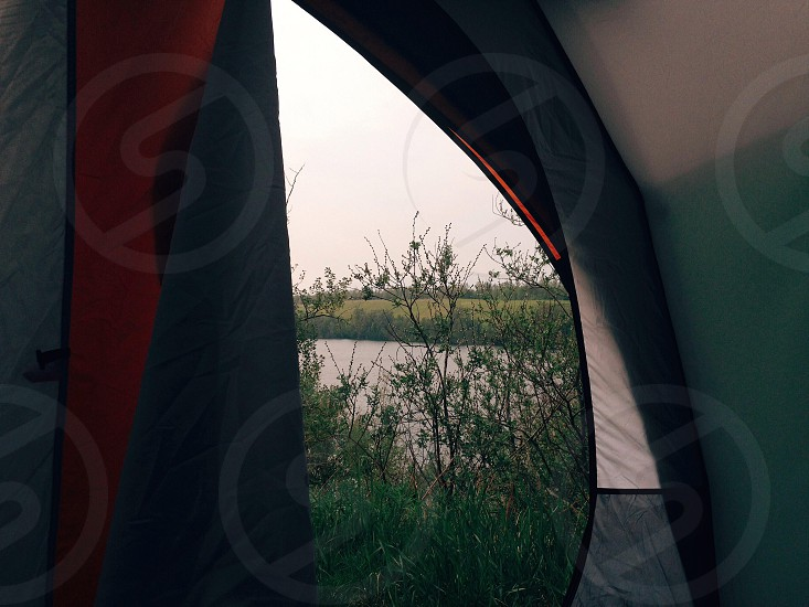 View of a lake from inside a tent.  photo