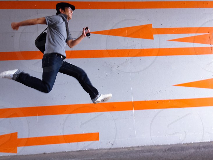 man in grey polo shirt and blue denim jeans jumping by a grey concrete wall with orange arrow decals photo