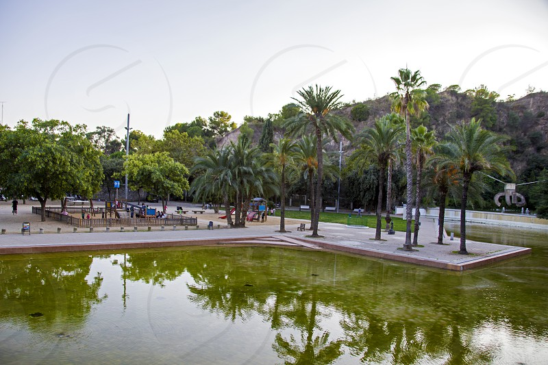 The park De La Creueta del Coll in Barcelona. This is one of the not very famous parks but it is very beautiful place because it is a forest park area and from the cliff located in the upper part of the park a stunning view of the sea mountains and the city. In the lower part of the park there is a beautiful recreation area with an artificial pond walking paths flowering plants benches for rest and a cafe photo
