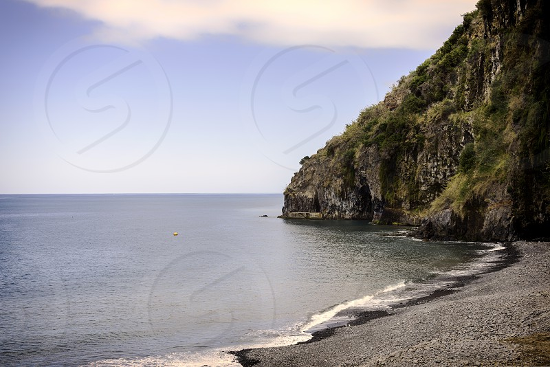 madeira coastline with ocean and rocks with calm sea and rocky beack photo