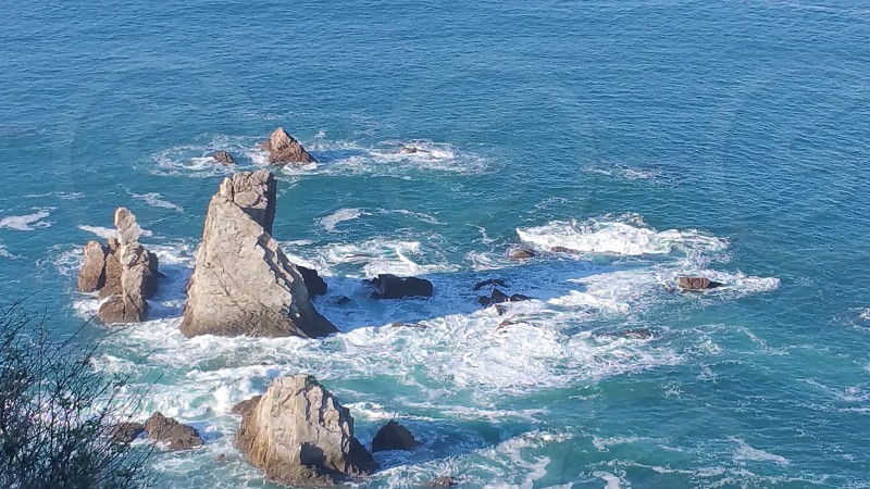 rocks in the blue water with waves photo