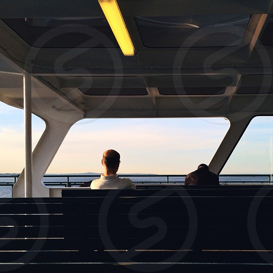 man in white collared shirt seating on bench on ship photo