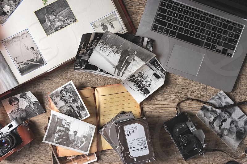 Old photo cards and old vintage album with vintage camera on wooden background photo