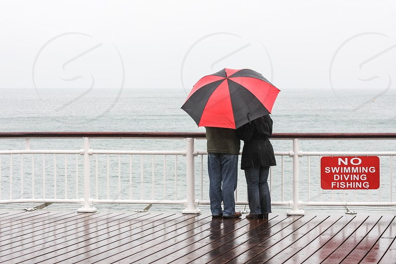 """A couple seen from behind holding an umbrella and watching the sea on a rainy day in England. A sign post says ;""""no swimming diving fishing"""". photo"""