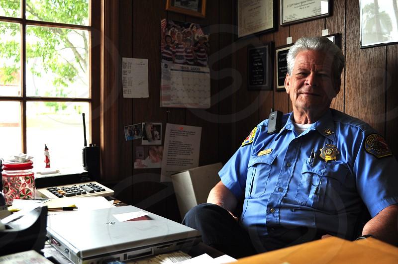 man wearing police uniform sitting photo