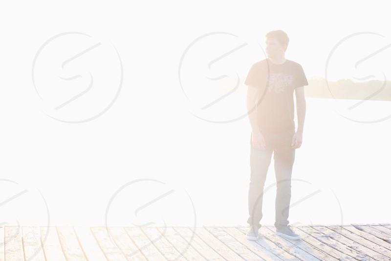 man standing on brown wooden foot bridge photo