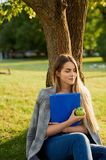 Pretty girl with her book in park background sunset photo