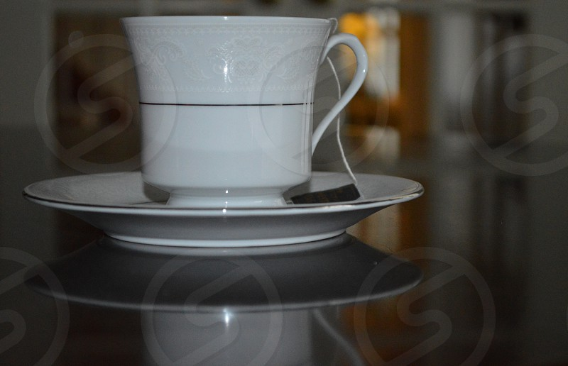 white ceramic tea cup on white ceramic saucer photo