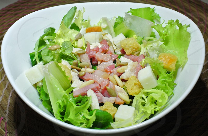 Delicious Caesar salad with bacon bits and pine nuts photo