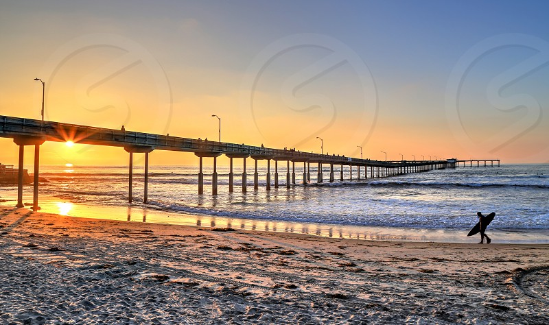 A surfer walks on Ocean Beach near the pier in San Diego California. photo