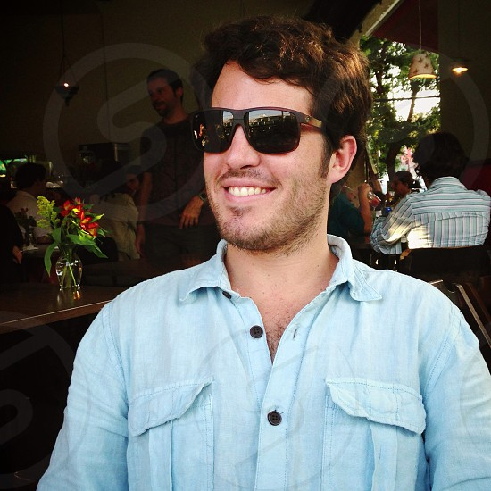 man in blue denim button up shirt with black sunglasses sitting photo