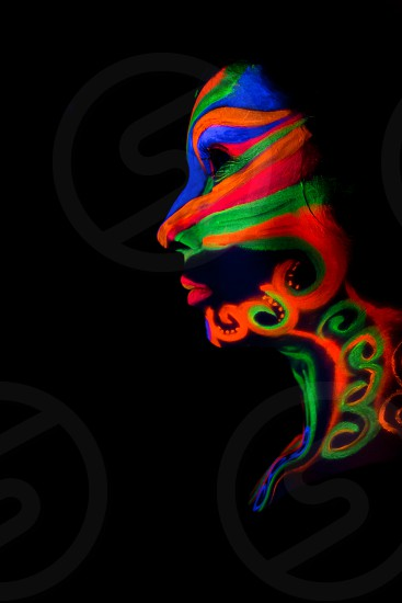 Woman with make up art of glowing UV fluorescent powder. photo