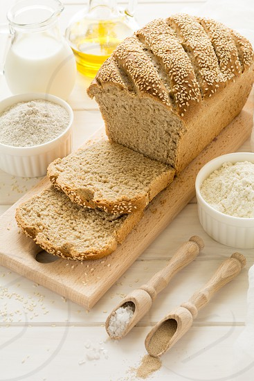 Ingredients for homemade wheat and rye bread with sesame seeds on white wooden table. Selective focus photo
