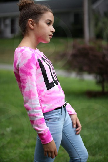 girl in white and pink long sleeve shirt with black print standing photo