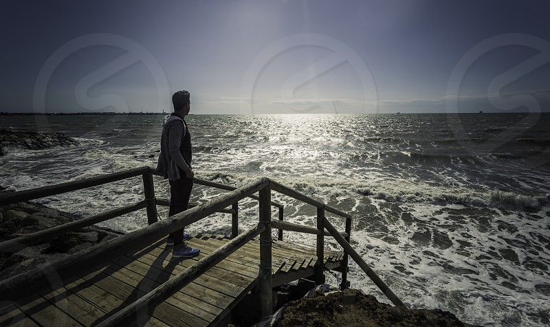 Young adult man standing on the jetty looking at the sea photo