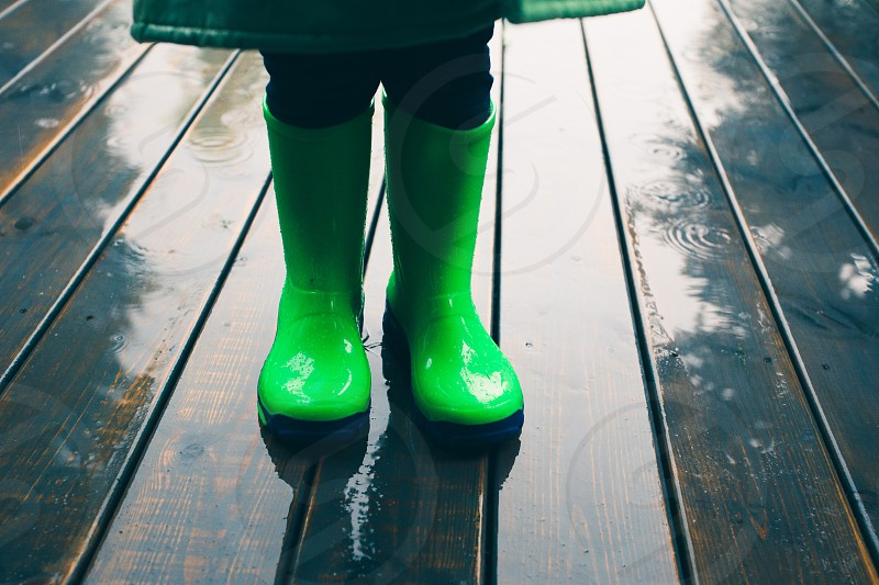 Closeup of legs of kid standing on a porch wearing green wellies and raincoat. Rain boots in bright green color photo