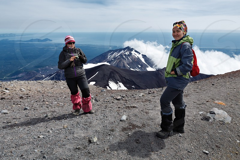 AVACHA VOLCANO KAMCHATKA PENINSULA RUSSIA - AUG 7 2014: Two young women tourists stand of top of crater of active Avachinsky Volcano on background of cone of Kozelsky Volcano and Pacific Ocean. photo