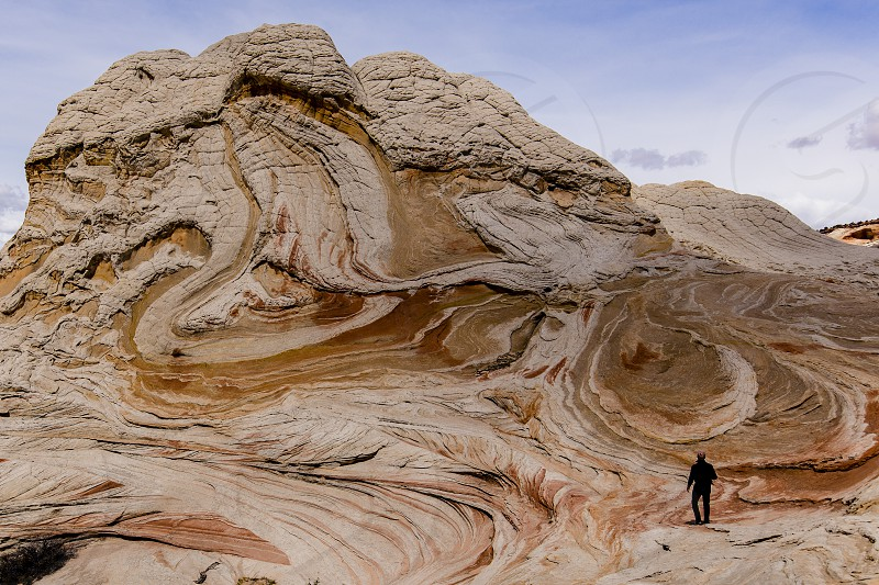 Man facing away looking at enormous mass of swirling and weathered sandstone rock formation. photo