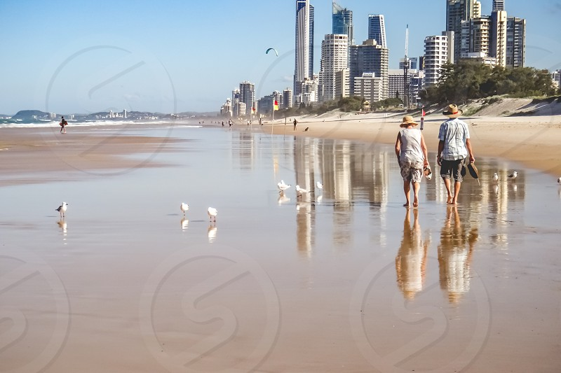 rear view of an active senior couple on vacation taking a leisurely walk at the beach Gold Coast Australia  photo