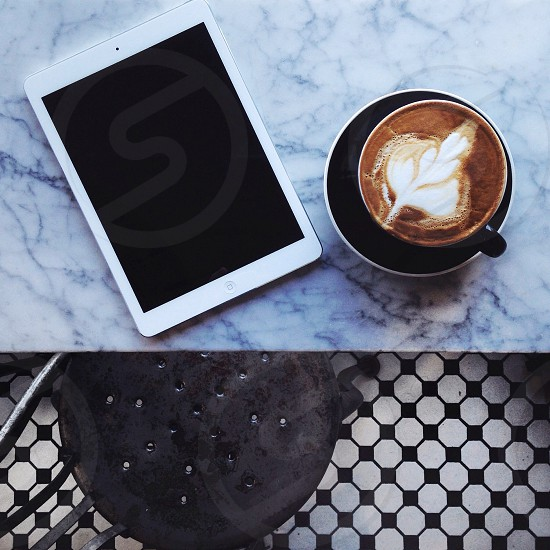 leaf foam cappuccino coffee in black ceramic mug with saucer beside white ipad on blue counter top photo