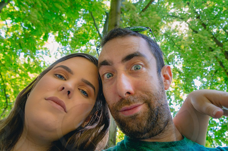 Happy young couple taking a selfie with a smartphone or camera at the park. They looking down while making silly and funny faces. photo
