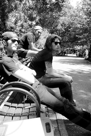 three men sitting on bench photo