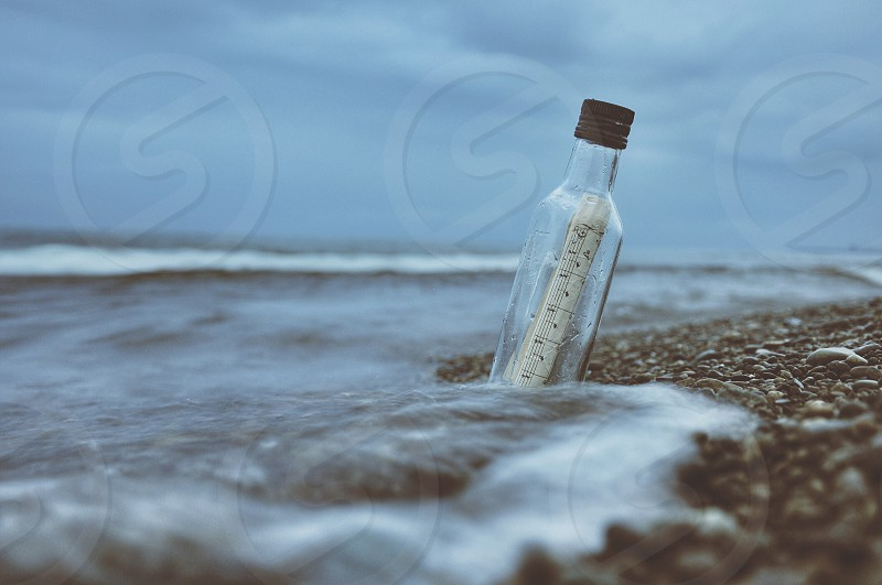 letter on glass bottle on seashore in macro photography photo