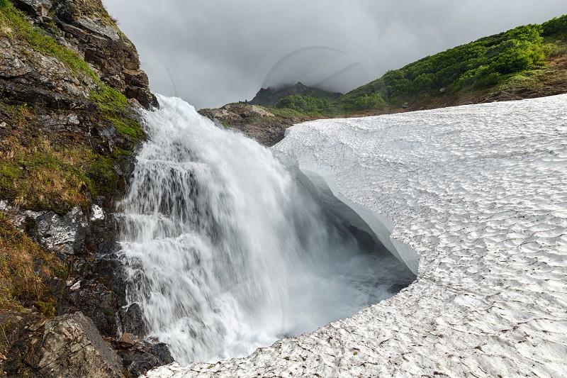 Amazing mountain landscape of Kamchatka: summer view of beautiful waterfall falling into the snowfield in Mountain Range Vachkazhets. Eurasia Russia Far East Kamchatka Peninsula. photo