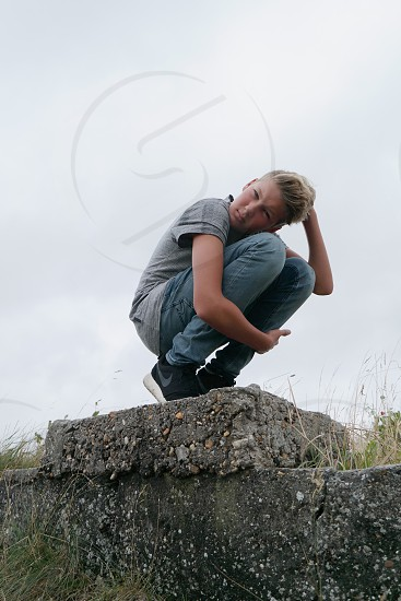 boy in grey shirt sitting point toe on the concrete floor during daytime photo