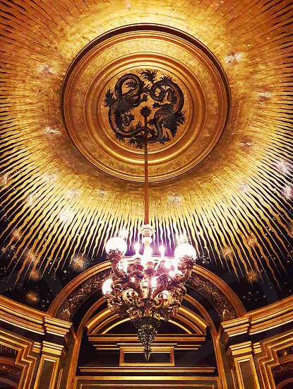 Beautiful Golden ceiling and a chandelier inside the Opera Garnier Palace in Paris France. photo