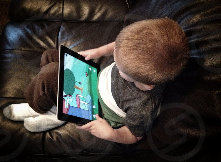 boy holding black tablet computer photo