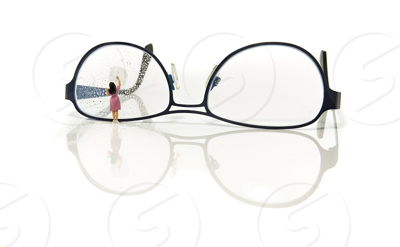 cleaning glasses by little world miniature woman figure photo