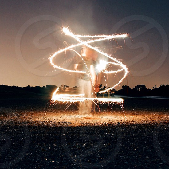 person swirling sparkler at night photo