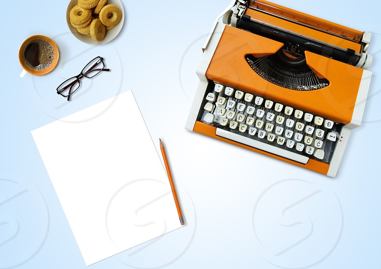 Typewriter on light blue background with coffee empty sheet of paper eyeglasses and cookies table top view photo