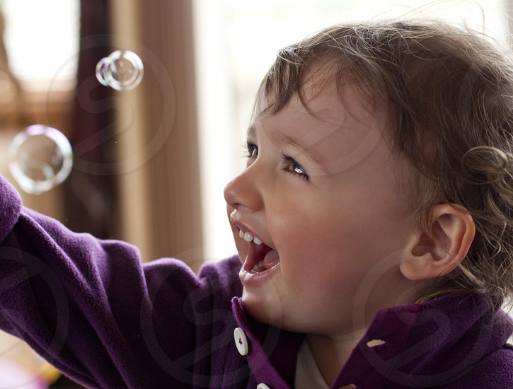 Joyful toddler playing with floating soap bubbles.  Toddler wearing purple sweater. photo