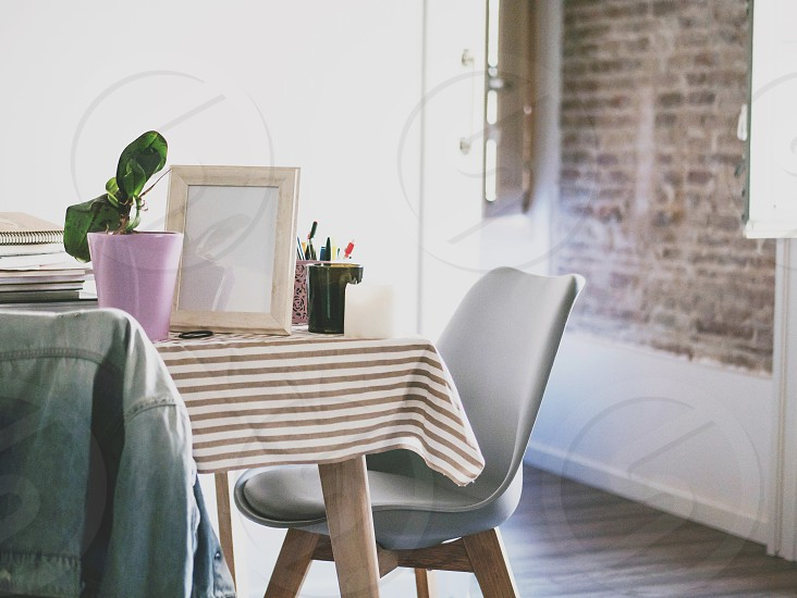 Modern table with flower photo frame and stationery in cozy flat. Living room interior and home decor concept photo
