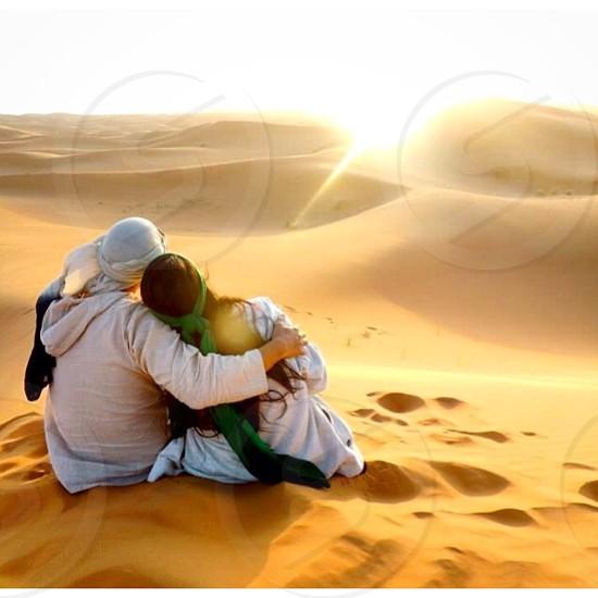 man and woman sitting on desert photo