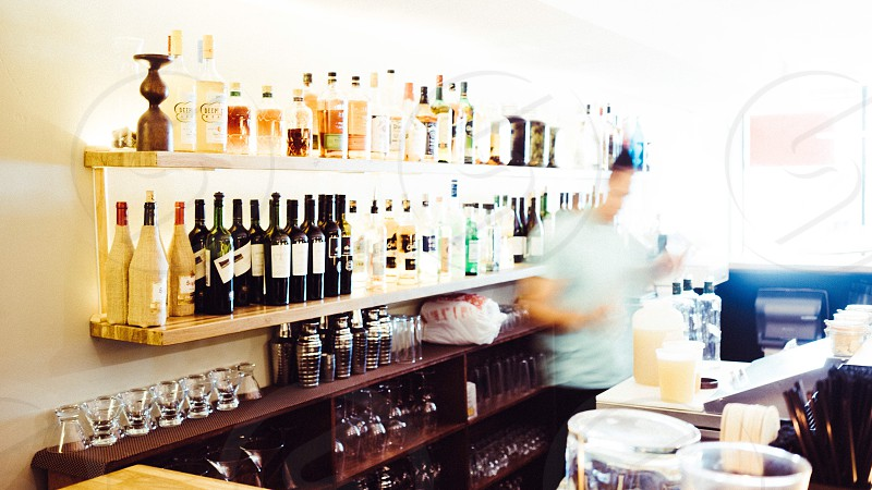 person standing beside counter and shelf full of liquor bottles photo