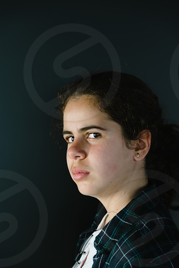 Headshot portrait of defiant teenager looking at camera side view photo